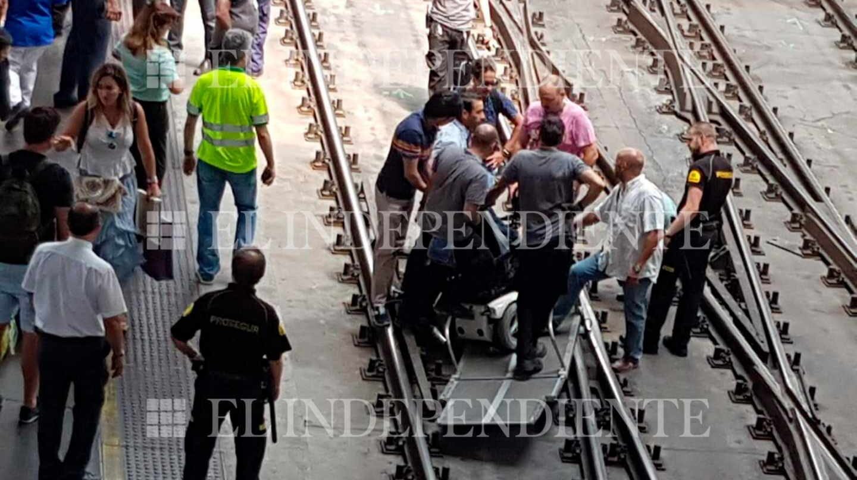 Varias personas en las vías de Atocha rodean la rampa habilitada para las personas con movilidad reducida.