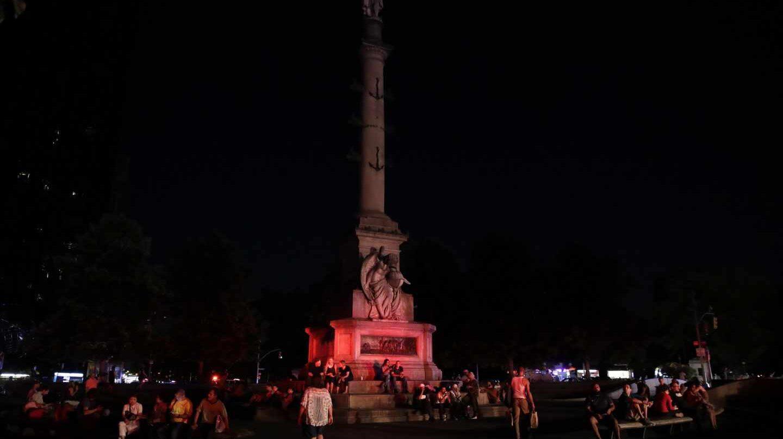 Personas sentadas en el Círculo de Columbus de Manhattan durante el apagón.
