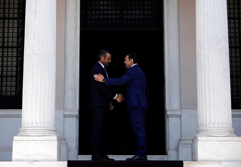 Kyriakos Mitsotakis, izqda, primer ministro de Grecia, y el jefe del gobierno saliente, Alexis Tsipras, se dan la mano en el Palacio Presidencial de Atenas.