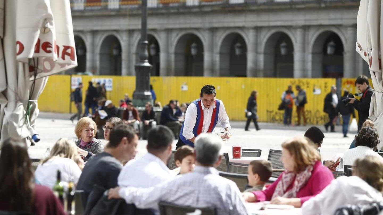 Un camarero sirve mesas en una terraza de Madrid.