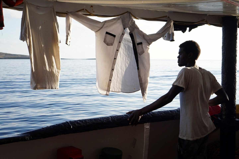 """Un migrante mira este domingo desde la cubierta de el buque """"Open Arms"""" las costas de Lampedusa (Italia)"""