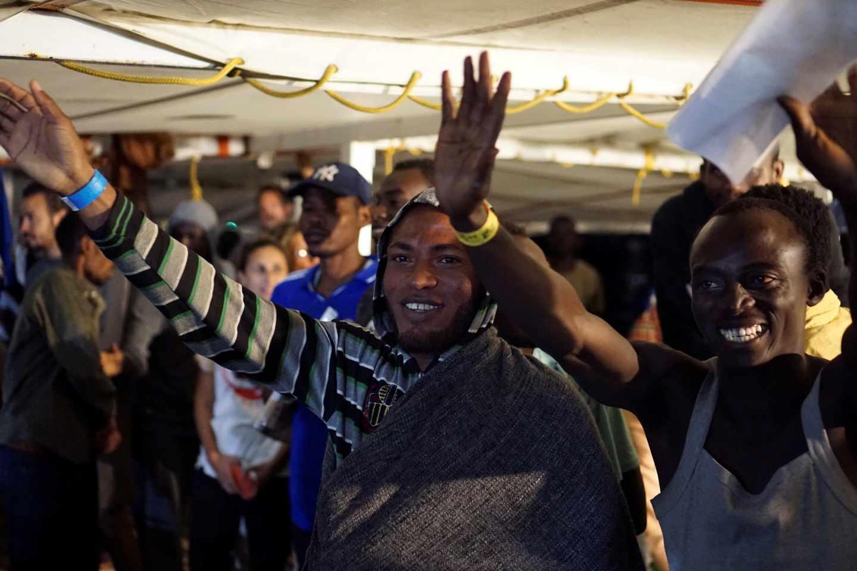 Los inmigrantes del Open Arms celebran la llegada a Lampedusa.