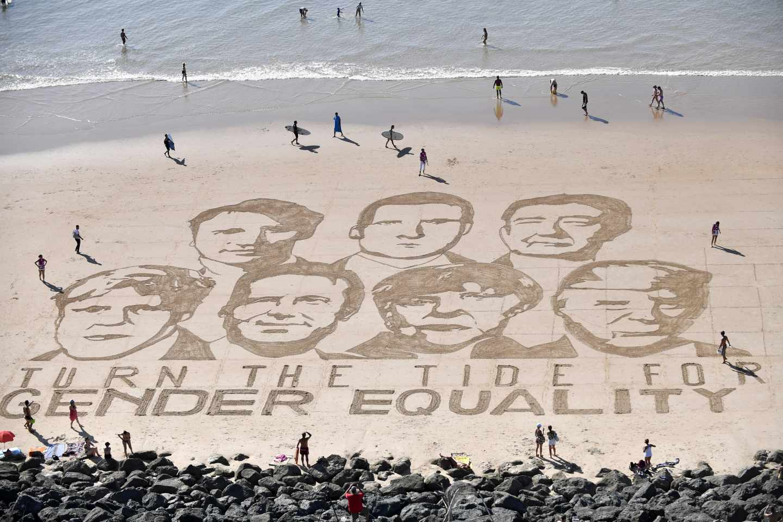 """Vista aérea de un mensaje escrito en la arena de la playa Côte des Basques en Biarritz: """"Que cambie la marea por la igualdad de género"""""""