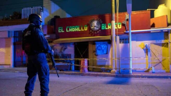 Un agente de la policía custodia en las primeras horas de este miércoles frente al bar El Caballo Blanco.