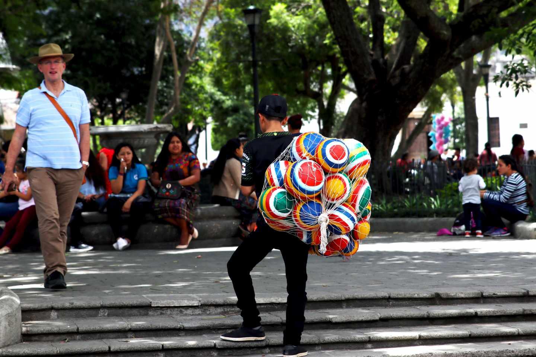Un hombre vende pelotas de caucho en la plaza central