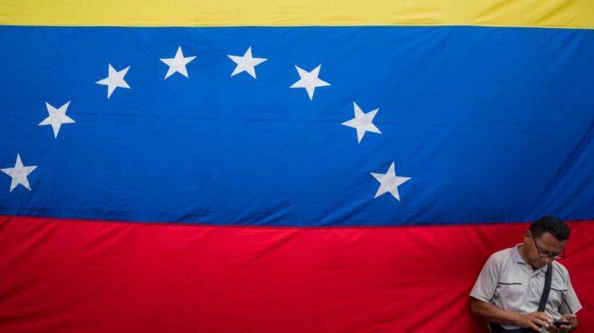 Un venezolano revisa su móvil junto a una gran bandera de la República Bolivariana, en Caracas.