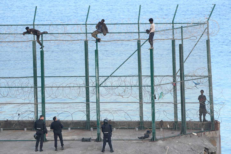 Migrantes, encaramados en la valla fronteriza de Ceuta.