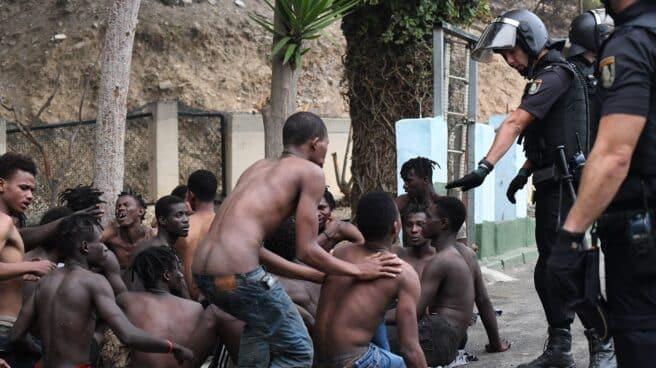Uno de los de 153 migrantes, levanta los brazo a su entrada en Ceuta saltando su doble valla en lo que ha sido la primera incursión en grupo en un año.