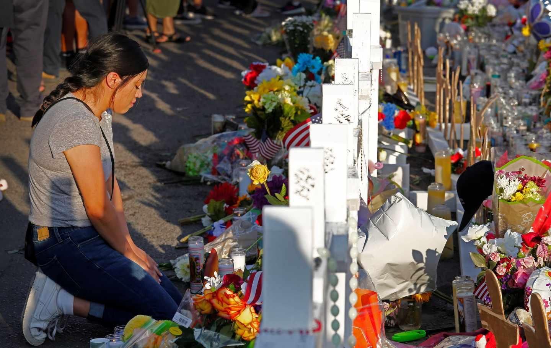 Una mujer se arrodilla ante las cruces en recuerdo de las víctimas mortales en El Paso.