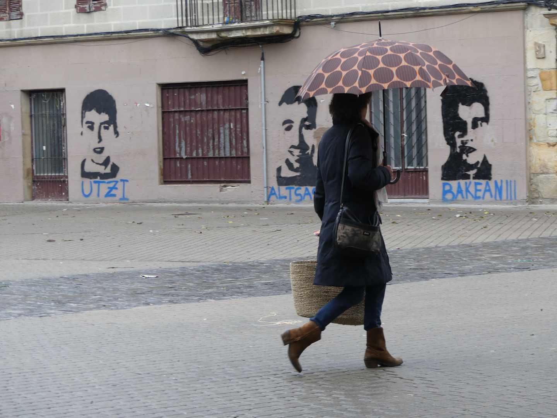 Una mujer pasa frente a los retratos de tres de los condenados.