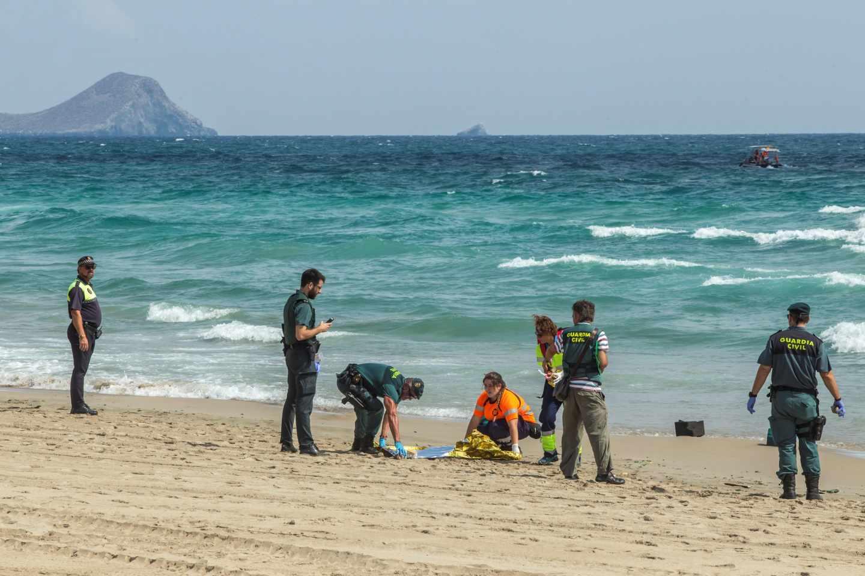 Agentes de la Guardia Civil y miembros de los servicios de Emergencias buscan restos del aparato siniestrado en una playa de la zona.