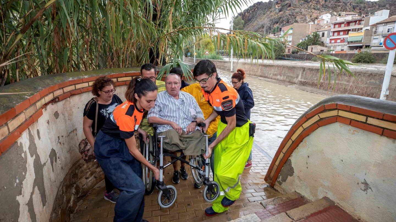 Voluntarios de protección civil trasladan a un hombre en silla de ruedas tras las intensas lluvias esta tarde en el barrio de Runes, Blanca, (Murcia)