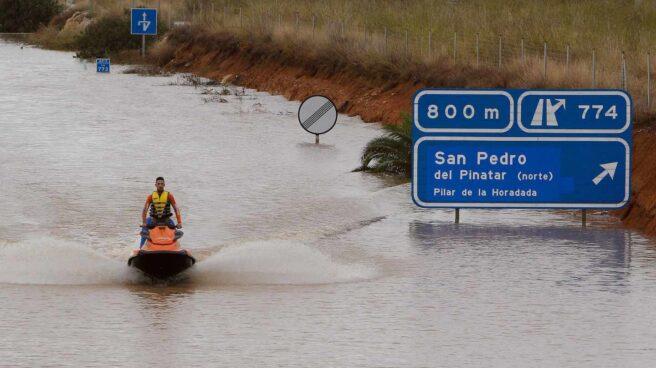 Un miembro de los servicios de rescate cruza la autopista AP-7 en moto acuática