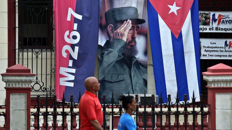 Dos cubanos pasan ante un gran cartel de Fidel en una conmemoración del Asalto al Cuartel Moncada.