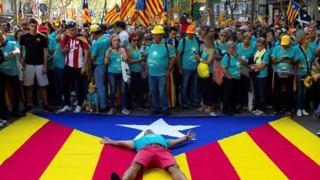 Un manifestante, tumbado sobre una estelada durante la Diada de 2019.