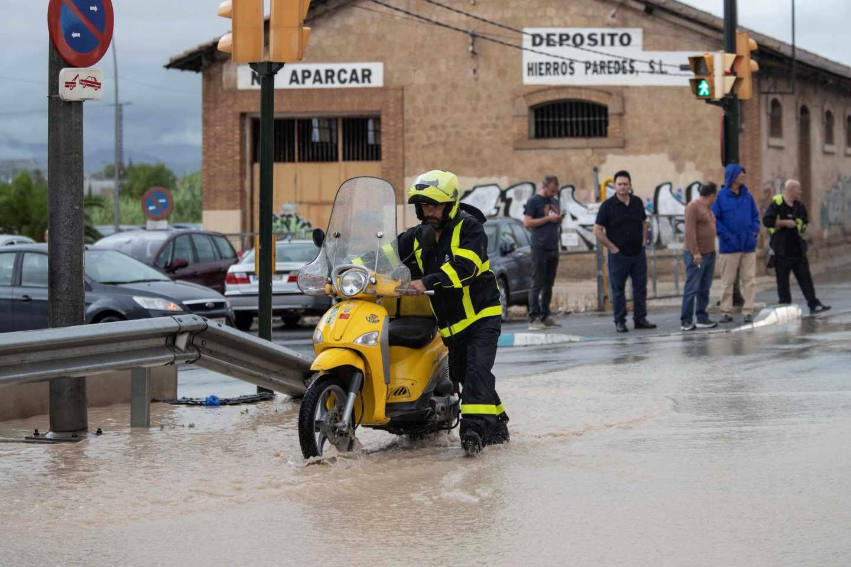 Un cartero empuja su moto en Molina de Segura, (Murcia), inundada por las intensas lluvias.