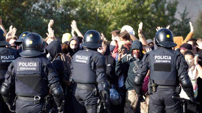 Agentes de Mossos d'Esquadra desalojan a manifestantes que cortaban el tráfico durante las protestas de Cataluña.