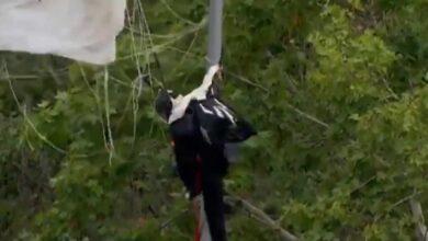 Un paracaidista queda enganchado en una farola durante el desfile del 12 de octubre