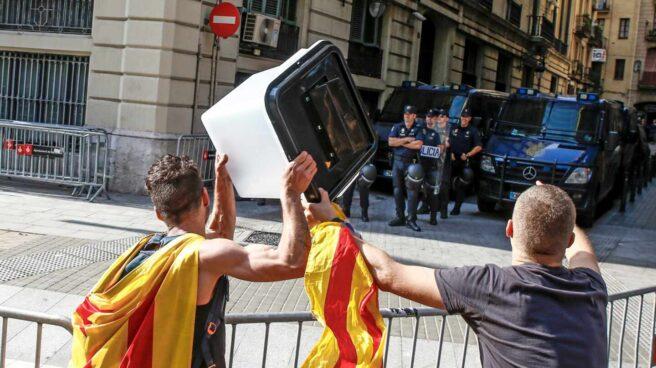 Dos jóvenes independentistas muestran esta semana una urna empleada el 1-O a los policías nacionales apostados ante la Jefatura Superior de Barcelona.
