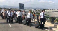 El personal de vuelo de Emirates accede a pie al aeropuerto del Prat por el bloqueo