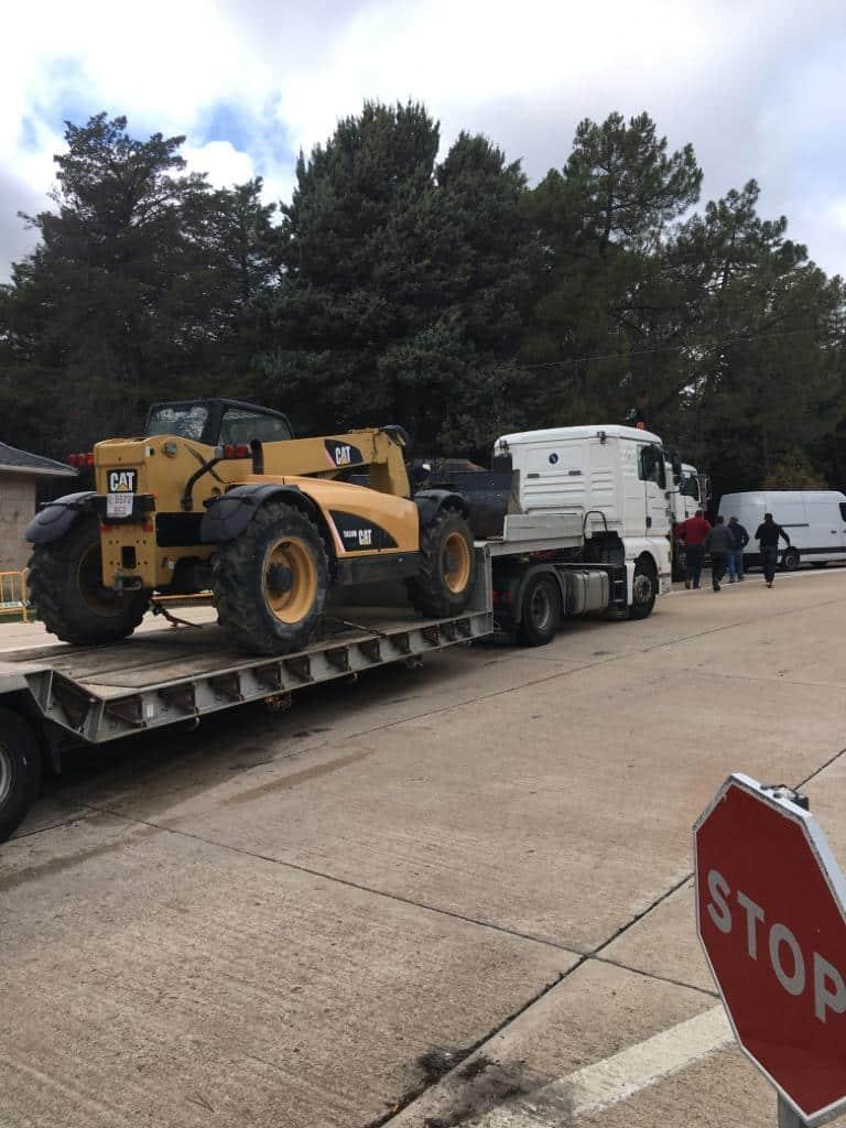 Un camión transporta una excavadora hasta el Valle de los Caídos.