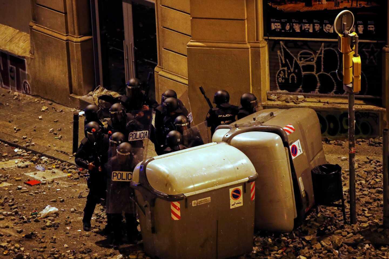 Un grupo de antidisturbios, parapetados tras unos contenedores junto a la Plaza de Urquinaona (Barcelona) en medio de un manto de piedras durante los altercados de octubre.