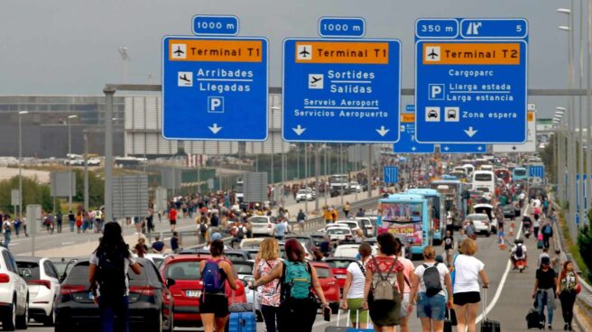 Pasajeros acceden a pie al aeropuerto de El Prat por el corte de los accesos por manifestantes independentistas.