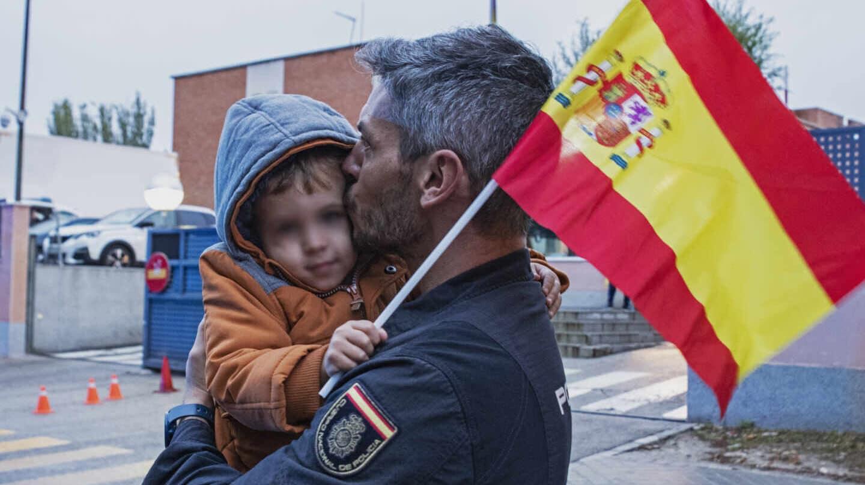 Un policía nacional besa a su hijo a su regreso a Madrid, este martes, tras intervenir en el refuerzo en Cataluña.