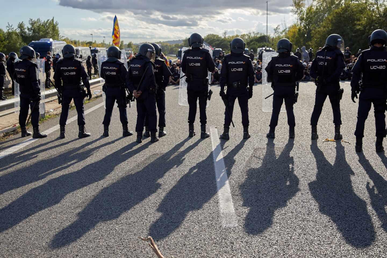 Policías nacionales, desalojando a los manifestantes que cortaban el tráfico en la AP-7 en Girona.