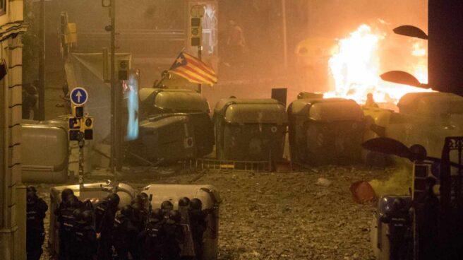 Policías nacionales, parapetados este viernes tras unos contenedores ante una de las barricadas levantadas por los violentos en Barcelona.