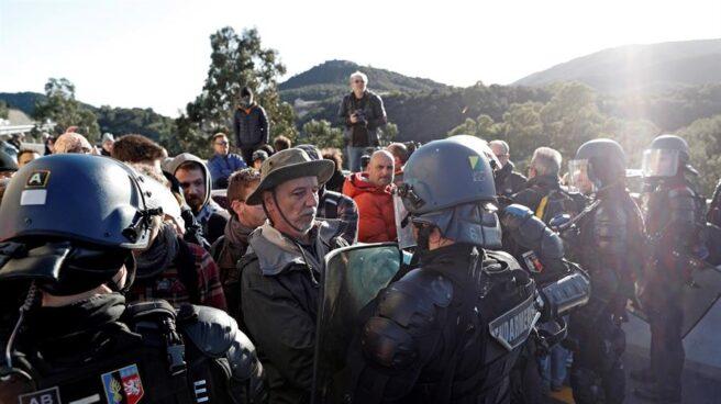 Gendarmes franceses tratan de desbloquear el corte de la autopista que enlaza España y Francia en el paso de Le Perthus (Francia).