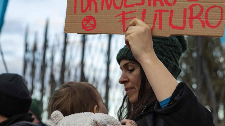 Una mujer protesta en la puerta de la Cumbre del Clima con un bebé en brazos