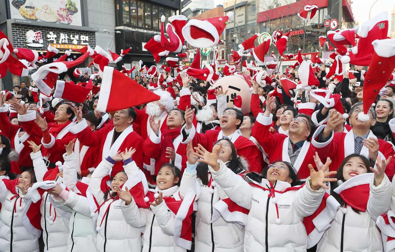 Decenas de niños y adultos lanzan al aire sus gorros de Santa Claus para celebrar la Navidad y el inicio de programas de voluntariado para los más necesitados en Corea del Sur.