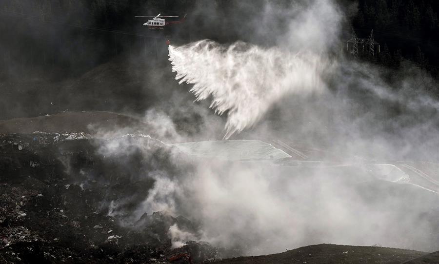 Un helicóptero arroja agua sobre un incendio ocasionado en el vertedero de Zaldibar.