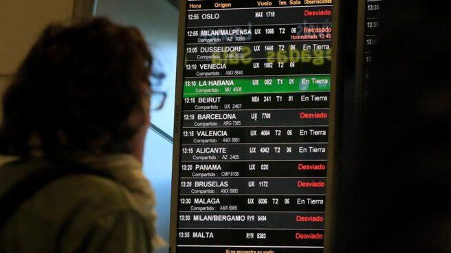 Un pasajero consulta los paneles de Barajas con los vuelos desviados por el cierre del espacio aéreo.