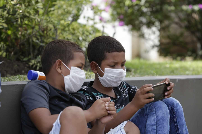 Dos niños con mascarillas juegan con un teléfono móvil en Panamá