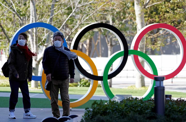 Dos personas con mascarilla caminan en la entrad del Comité Olímpico de Japón