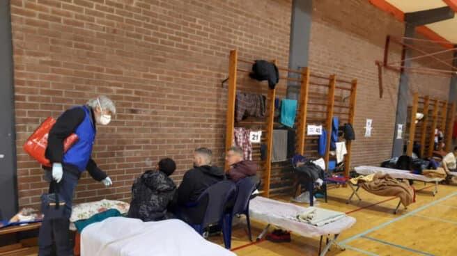 Trabajadores de Gizakia asisten a varios de los hombres acogidos en un polideportivo de Bilbao.