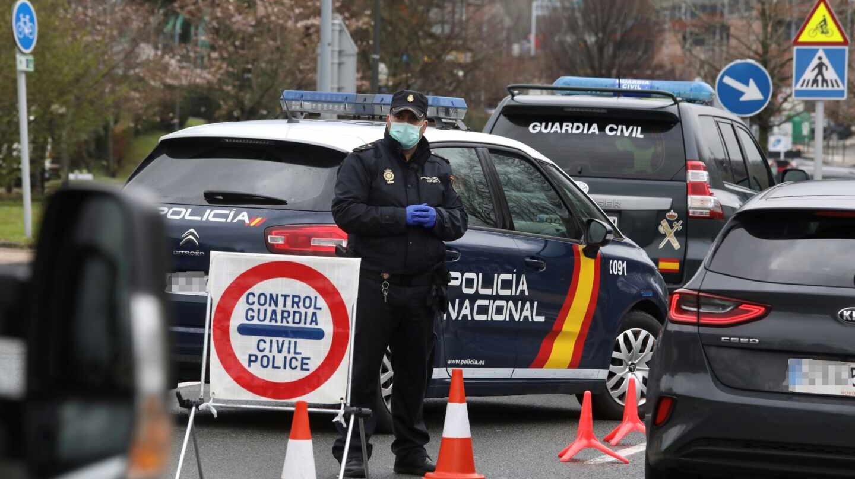 Un policía nacional se protege con una mascarilla en uno de los controles de frontera establecidos tras declararse el estado de alarma.