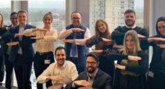 Hombres y mujeres del Banco Santander haciendo el símbolo de la igualdad