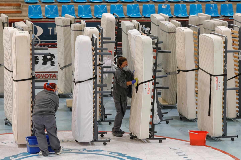 """Dos mujeres limpian y desinfectan camas que han sido cedidas por varios hoteles para habilitar el pabellón de deportes """"Les Comes"""" de Igualada."""