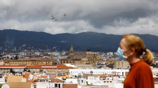 Una mujer camina con el fondo de la Mezquita-Catedral de Córdoba y un cielo cubierto de nubes oscuras.