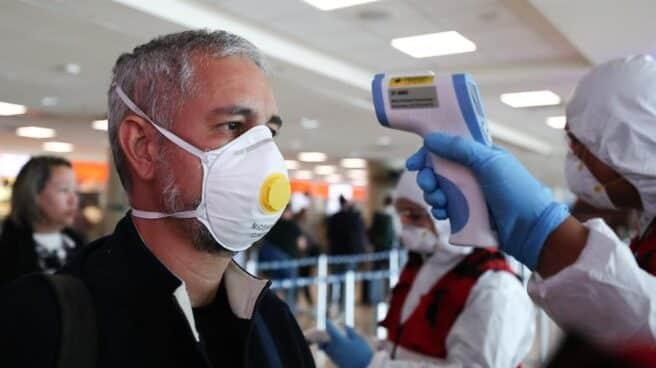 Un hombre con mascarilla pasa un control en el aeropuerto de Quito