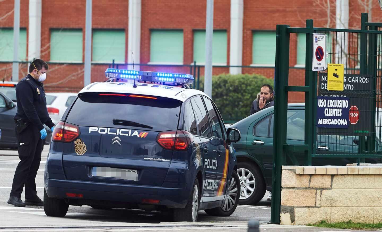Un policía nacional, protegido con una mascarilla, junto al aparcamiento de un supermercado en Santander.