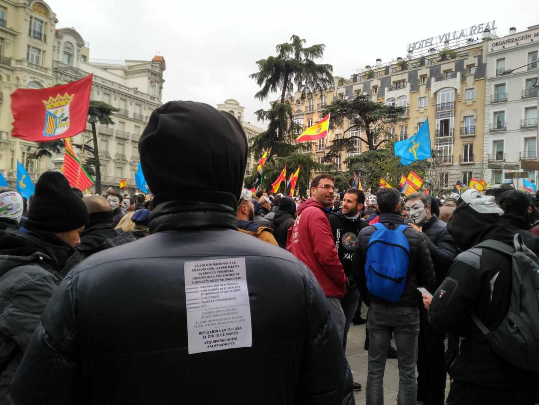 Un manifestante en la concentración convocada por Jusapol, con la octavilla que llama a 'reflexionar en casa' el 10 de marzo.