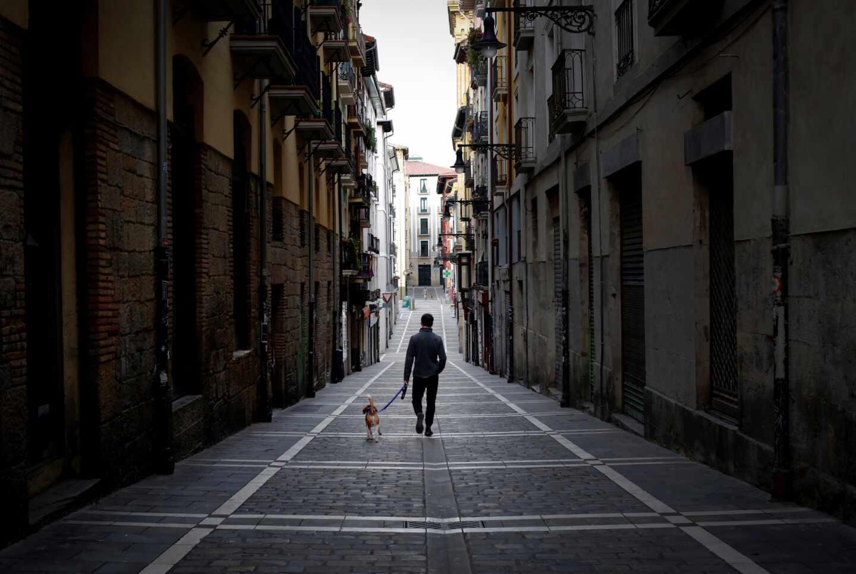 Un hombre pasea a un perro en Pamplona durante el confinamiento