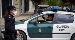 Un patrullero de la Guardia Civil pasa junto a una funcionaria del Cuerpo Nacional durante el estado de alarma.
