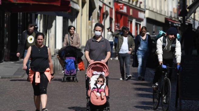 Una familia con un niño en un carrito por las calles de París a principios de este mes de abril.