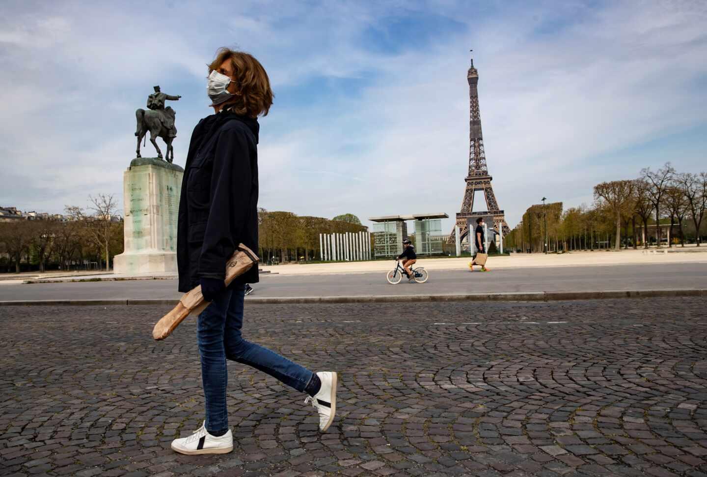 Una mujer pasa por delante de la Torre Eiffel durante el confinamiento en París