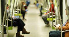 Dos hombres consultan sus teléfonos móviles en el transporte público.